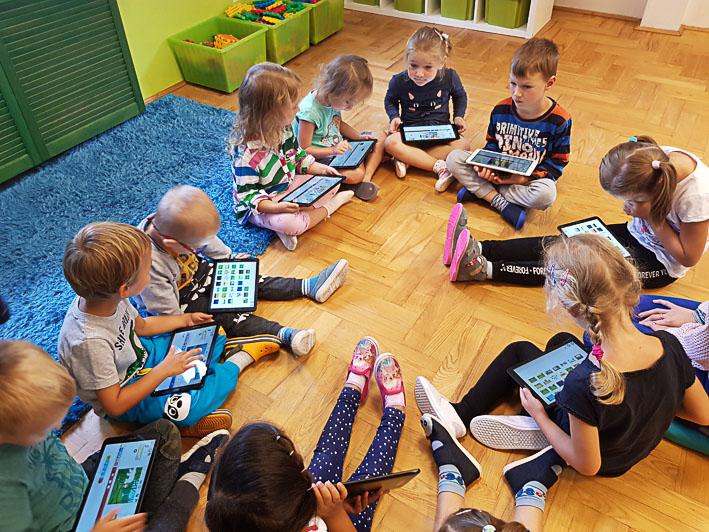 Dzieci bawią się tabletami w kółku w ramach dodatkowych zajęć w Owocowym Przedszkolu na Ursynowie.