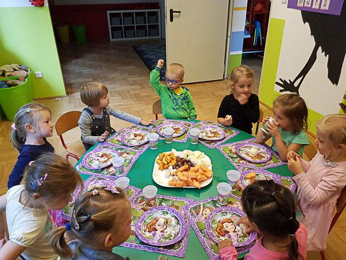 Grupa przedszkolaków świętuje urodziny swojej koleżanki
