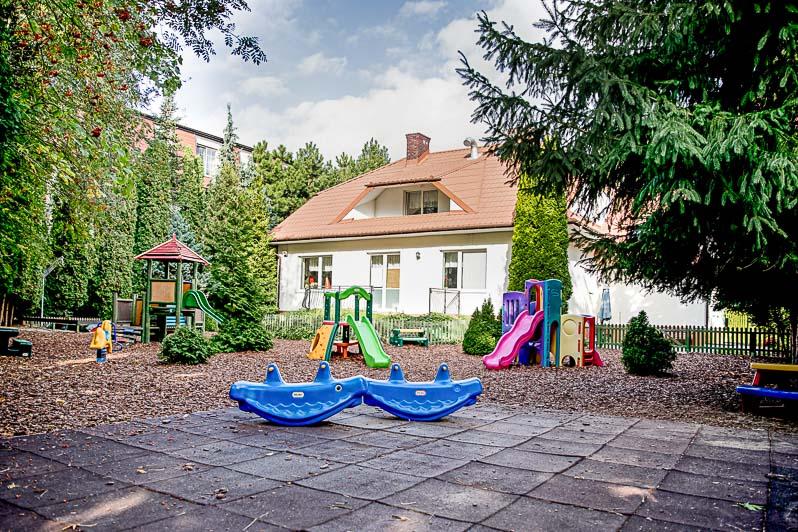 Plac zabaw na terenie przedszkola a za nim piękny budynek Owocowego Przedszkola.