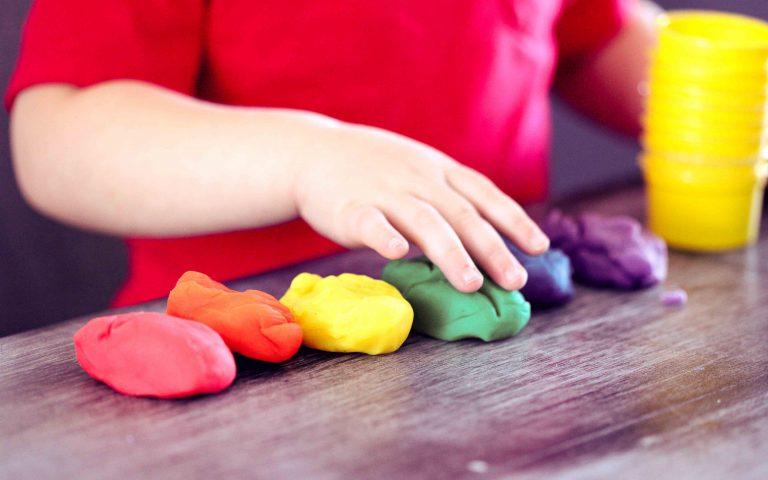 Dziecko bawi się plasteliną rozwijając swoje zdolności manualne w Owocowym Przedszkolu.