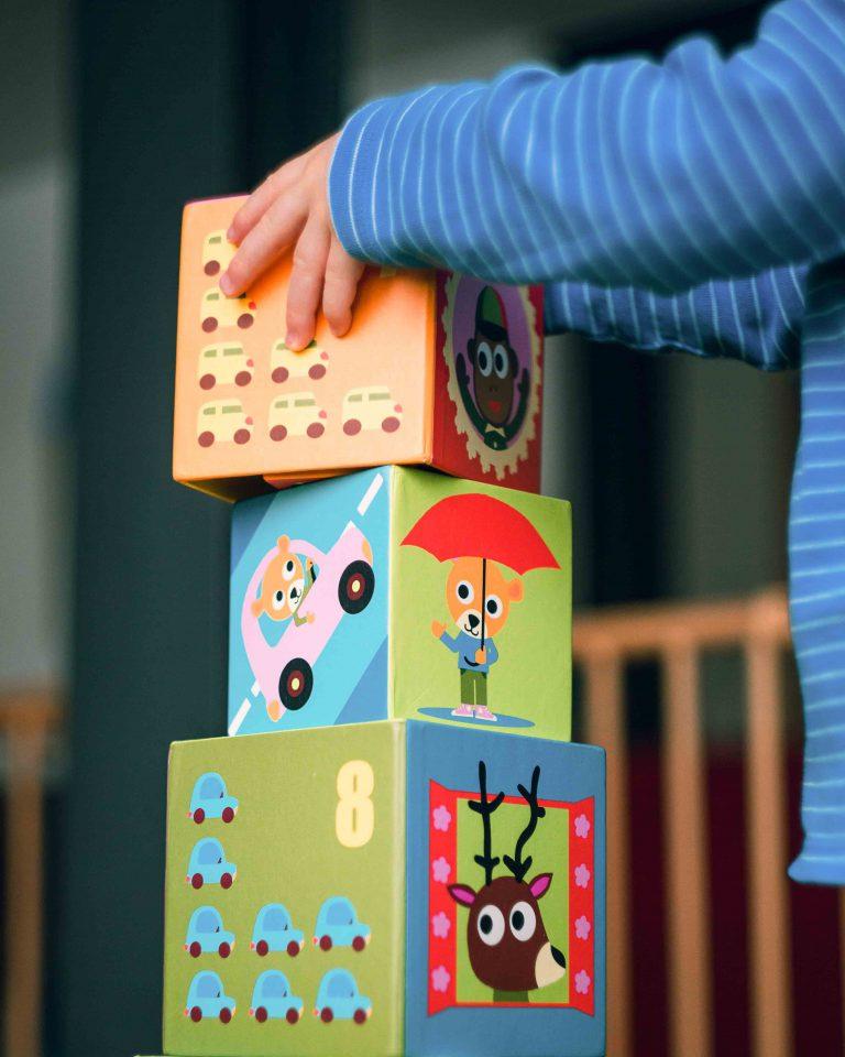 Dziecko układa wieże z klocków.