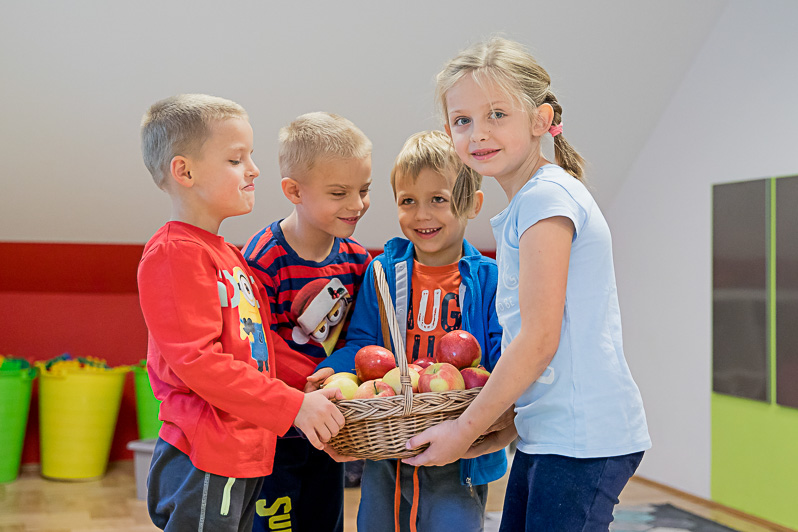 Dzieci bawią się razem trzymając koszyk pełen jabłek. Na ich twarzach widać emocje.