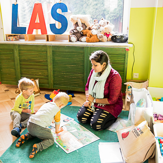 Na zdjęciu widać Panią przedszkolankę uczącą dzieci języka angielskiego.