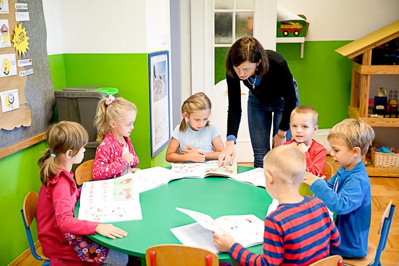 Dzieci wspólnie z nauczycielką rozwiązują zadania w ćwiczeniówkach.