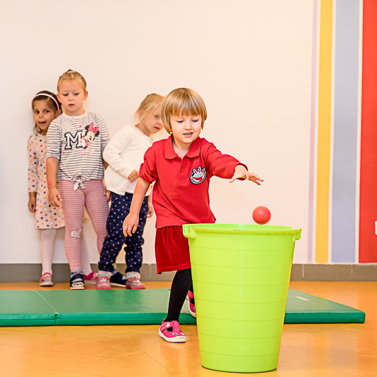Dziewczynka wrzuca piłeczkę do koszyka na zajęciach z integracji sensorycznej.