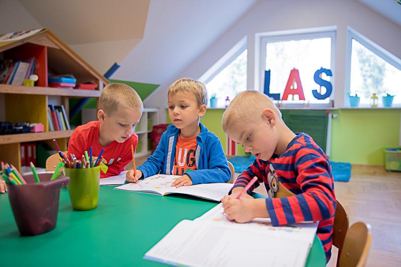 Trójka chłopców z dużym zaangażowaniem rozwiązuje zadania z ćwiczeniówek.