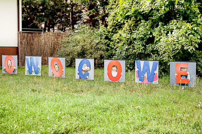 Napis owocowe na trawniku przed wejściem do przedszkola.