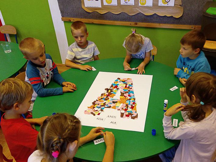 Przedszkolaki układają literkę a z kolorowych kawałków kartki. Układają obok słowa na zaczynające się na litere A.