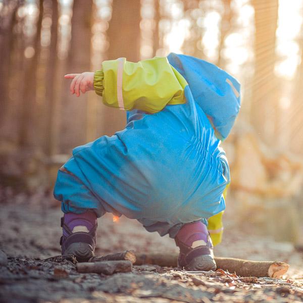 chłopiec bawiący się w lesie